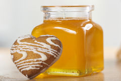 Heart-shaped cookies and a jar of honey. On the table Royalty Free Stock Photography