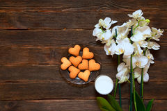 Heart-shaped cookies, milk and orchid on a dark wooden backgroun. D.  Valentine's Day. Concept of care Stock Image