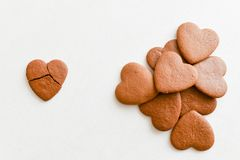 Heart shaped cookies, one of them is broken on a white background. Crack heart-shaped cookies as a concept of unsuccessful stock images