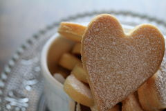 Heart shaped cookies. Powdered heart shaped cookies on a glass plate Royalty Free Stock Photos