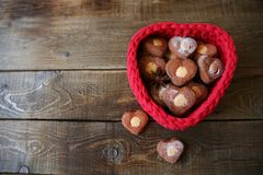 Heart-shaped cookies in a red heart-shaped basket on a wooden background with copy space for text royalty free stock image