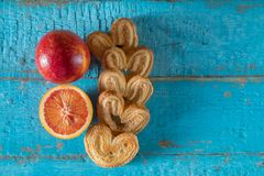 Cookies in the shape of a heart with decorative slices of dried apples on blue wooden surface. Heart shaped cookies with red orange on a blue wooden surface with Royalty Free Stock Image