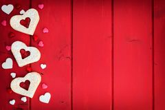 Heart shaped cookies side border over red wood Royalty Free Stock Image