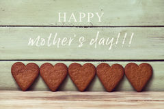 Heart-shaped cookies and text happy mothers day. The text happy mothers day and of some heart-shaped cookies in line against a pale green rustic wooden Stock Image