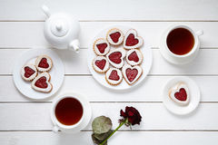 Heart shaped cookies for Valentines day with teapot, two cups of tea and rose composition Stock Photography