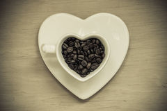 Heart shaped cup with coffee beans on wooden table Royalty Free Stock Photos