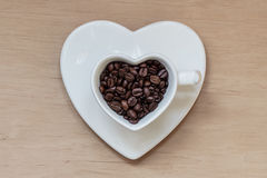 Heart shaped cup with coffee beans on wooden table Royalty Free Stock Photography