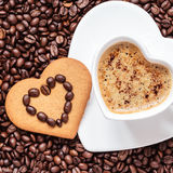 Heart shaped cup and cookie on coffee beans background Royalty Free Stock Photos