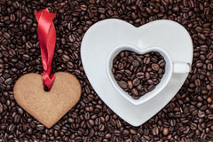 Heart shaped cup and cookie on coffee beans background Stock Photography
