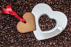 Heart shaped cup and cookie on coffee beans background Stock Image