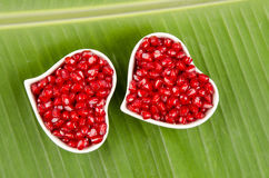 Heart shaped cup Pomegranate, Punica apple (Punica granatum L.)., On banana leaves. Stock Photos