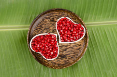 Heart shaped cup Pomegranate, Punica apple (Punica granatum L.)., On banana leaves. Stock Images