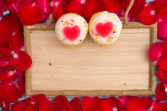 Heart shaped cupcake and red rose with wooden board Royalty Free Stock Photography