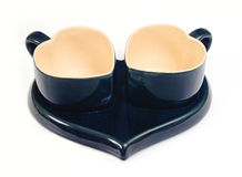 Heart-shaped cups. Two heart-shaped cups on the tea-tray on the white background Royalty Free Stock Photography