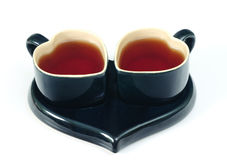 Heart-shaped cups. Two heart-shaped cups on the tea-tray on the white background Stock Photos