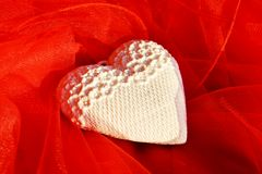 Heart shaped cushion. The white heart shaped cushion makes great contrast with the red soft texture of the support it is placed on royalty free stock photo