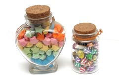 A heart-shaped and cylindrical glass bottle filled with handmade paper folded stars Royalty Free Stock Photo