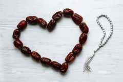 Heart shaped by dates and white rosary for Ramadan and Friday message concept stock photography