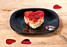 Heart shaped dessert. Dessert in the form of heart on a black saucer on a wooden table royalty free stock photo