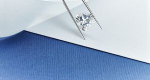 Heart Shaped Diamond Held in Tweezers Over Background in Blue and White