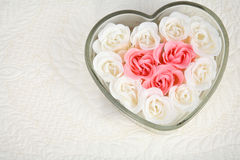 Heart Shaped Dish Filled with Ivory and Pink Roses. Close up of beautiful pink and ivory roses filling heart-shaped dish in upper right corner against a quilted stock photo