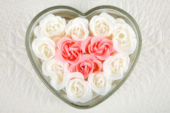 Heart Shaped Dish Filled with Ivory and Pink Roses. Close uo of beautiful pink and ivory roses fill heart-shaped dish against a quilted background stock photography