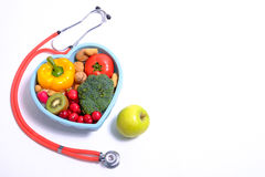 Heart shaped dish with vegetables and stethoscope Royalty Free Stock Image