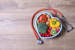 Heart shaped dish with vegetables and stethoscope  on wo Stock Photo