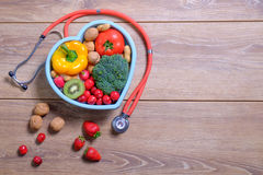 Heart shaped dish with vegetables and stethoscope  on wo Royalty Free Stock Image