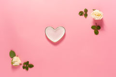 Heart-shaped dish with white rose frame. On a pink background Royalty Free Stock Photos