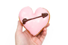 Heart Shaped Donut with Cupid's Arrow. Hand Holding a Heart Shaped Donut Isolated on a White Background royalty free stock photo