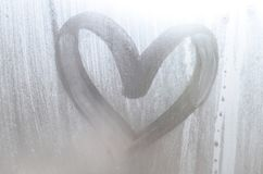 A heart-shaped drawing drawn by a finger on a misted glass in rainy weather royalty free stock photos