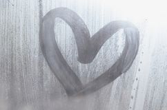 A heart-shaped drawing drawn by a finger on a misted glass in rainy weather.  stock photography