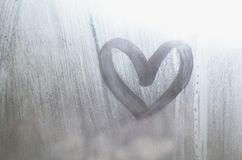 A heart-shaped drawing drawn by a finger on a misted glass in rainy weather royalty free stock photo