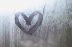 A heart-shaped drawing drawn by a finger on a misted glass in rainy weathe stock image