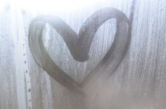 A heart-shaped drawing drawn by a finger on a misted glass in rainy weathe stock photography