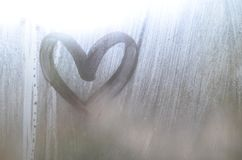 A heart-shaped drawing drawn by a finger on a misted glass in rainy weathe. R stock photo