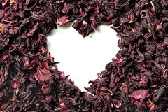 Heart shaped of dry hibiscus petals on white background royalty free stock photo