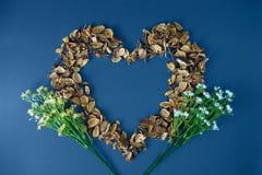 Heart shaped dry petals on blue background. Still life flat lay Stock Photo