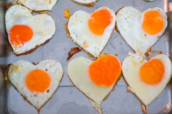 Heart shaped egg fire cooking Stock Photos