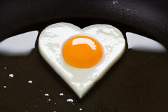 Heart shaped egg in a frying pan Stock Photos