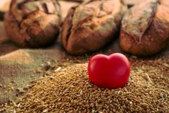 Heart shaped figure in rye and loaf of bread on background. Royalty Free Stock Photos