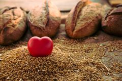 Heart shaped figure in rye and loaf of bread on background. Stock Images