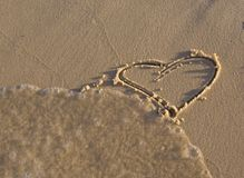 Heart shaped figurine on the sand Royalty Free Stock Images