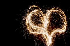 Heart shaped fireworks. Sparkling heart made of fireworks on black background royalty free stock image