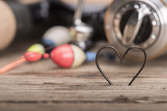 Heart shaped fishing hooks. And fishing tools Royalty Free Stock Photo