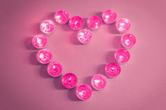 Heart shaped flaming pink tealight candles Royalty Free Stock Images