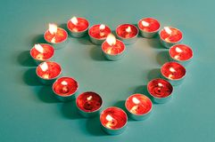 Heart shaped flaming red tealight candles Royalty Free Stock Photos