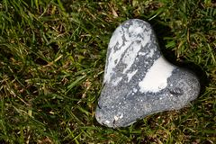 Heart shaped flintstone lying in the grass with copy space royalty free stock photography