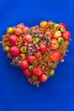 Heart-shaped Flower Arrangement. Heart-shaped dried flower and fruit arrangement on blue background stock images